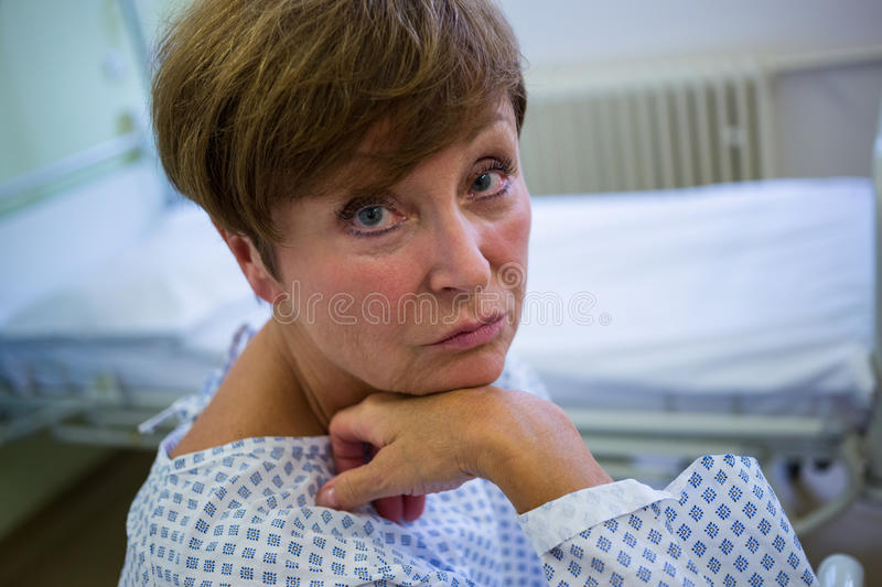 Portrait of sad senior patient sitting on a bed royalty free stock photo