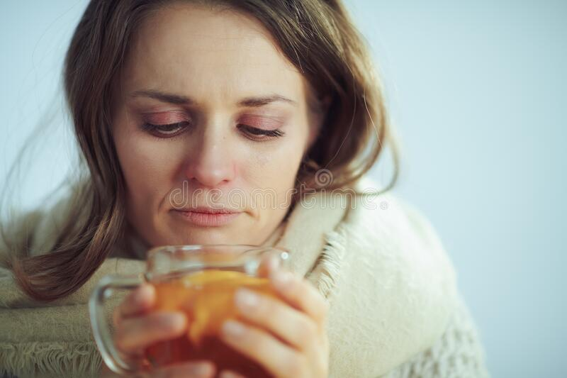Sad sick modern woman drinking cup of tea royalty free stock image