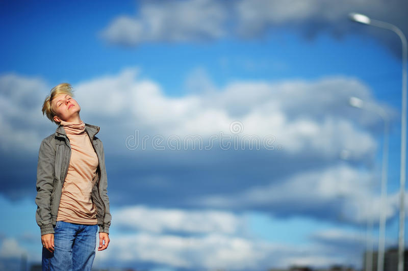 Portrait sad and stressed young woman suffering migraine headache, blue sky and clouds as background. stock images