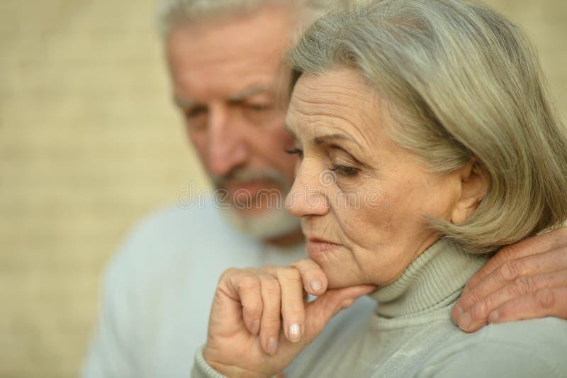 Portrait of sad thoughtful senior couple in park royalty free stock photos
