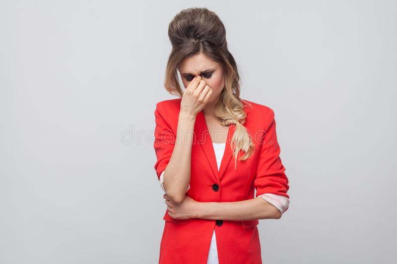 Portrait of sad unhappy beautiful business lady with hairstyle and makeup in red fancy blazer, standing touching her eyes and. Crying. indoor studio shot royalty free stock photography