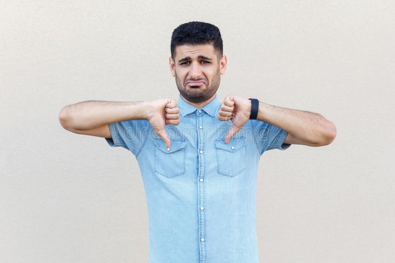 Portrait of sad, upset or worry handsome young bearded man in blue shirt standing, thumbs down and looking at camera with royalty free stock images