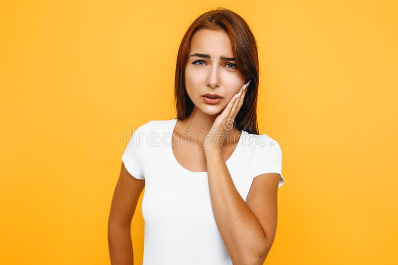 Portrait of sad woman having toothache and touching cheek. A girl suffering from painful toothache, frowning and touching her cheek, being displeased, standing royalty free stock image