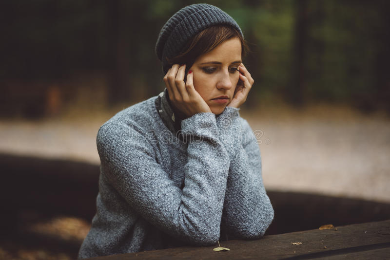 Portrait of sad woman sitting alone in the forest. Solitude concept. Millenial dealing with problems and emotions. stock images