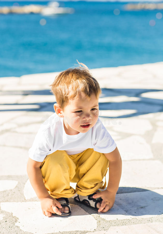 Portrait of a sad young boy thinking on the beach royalty free stock image