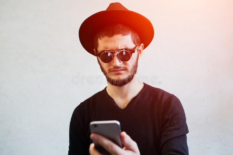 Portrait of sad young man looking shocked at smartphone.  royalty free stock photography