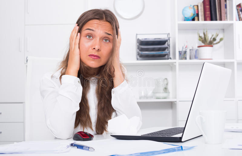 Portrait of sad young woman experiencing troubles. At work office royalty free stock photos
