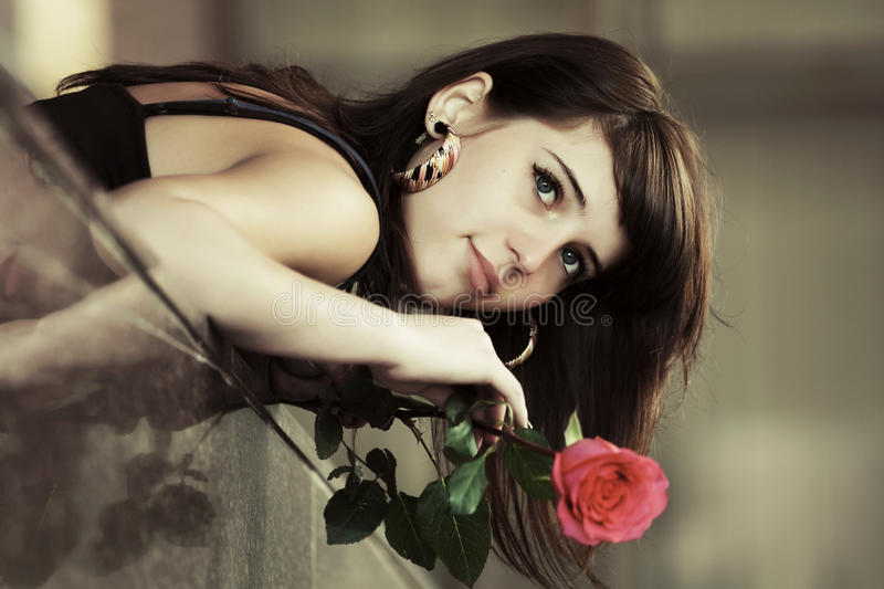 Portrait of sad young fashion woman with red rose stock image