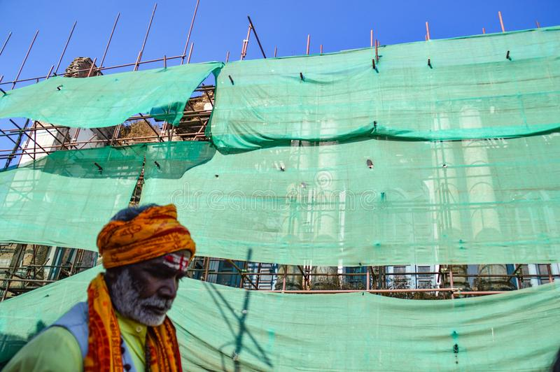 Rebuilding of culture. A portrait of a sadhu in the front of a scaffolding that conceals the Durbar sqaure after the earthquake. Sadhus are religious men who royalty free stock photos