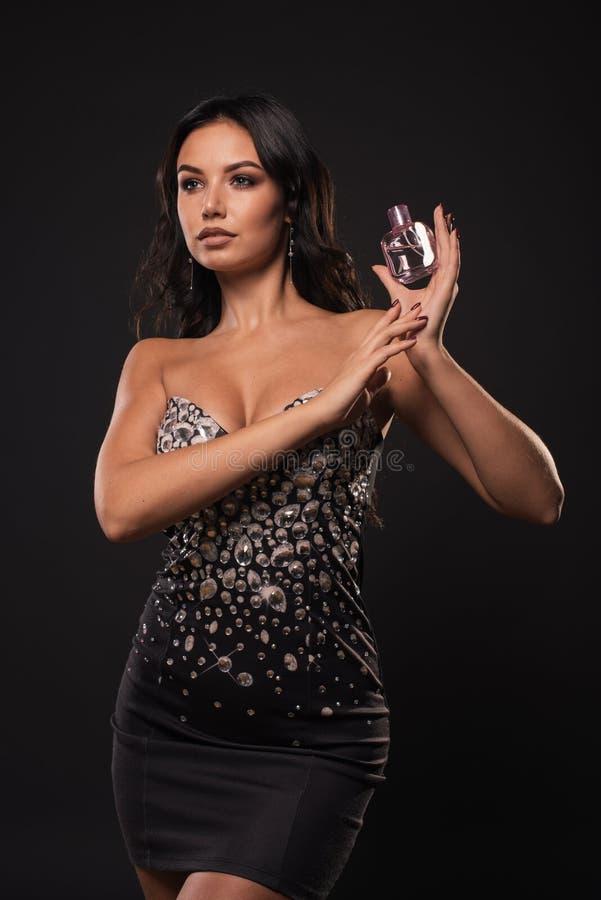 Portrait sans retoucher la belle femme avec la bouteille de parfum rose sur le fond foncé photographie stock