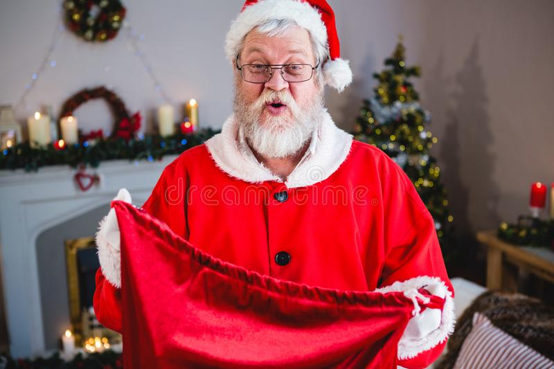 Santa claus holding gift sack at home. Portrait of santa claus holding gift sack at home stock photography