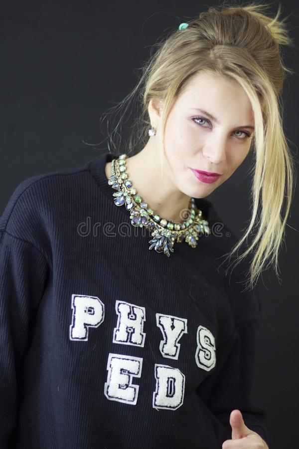 A portrait of a sassy blond woman with blue eyes and Phys Ed black shirt and necklace. stock images
