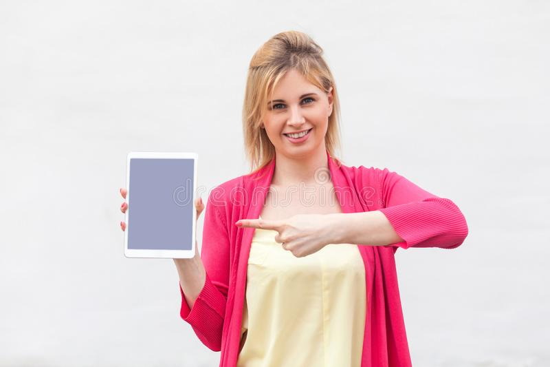 Portrait of satisfied beautiful young woman in pink blouse standing and holding tablet empty screen and pointing finger to device. With toothy smile and looking royalty free stock photography