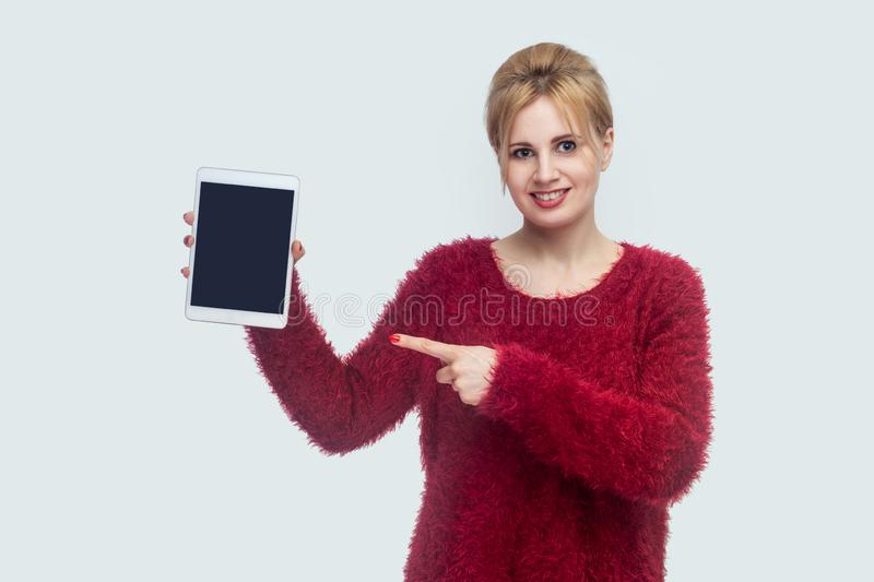Portrait of satisfied beautiful young woman in red blouse standing and holding tablet empty screen and pointing finger to device. With toothy smile and looking royalty free stock photo