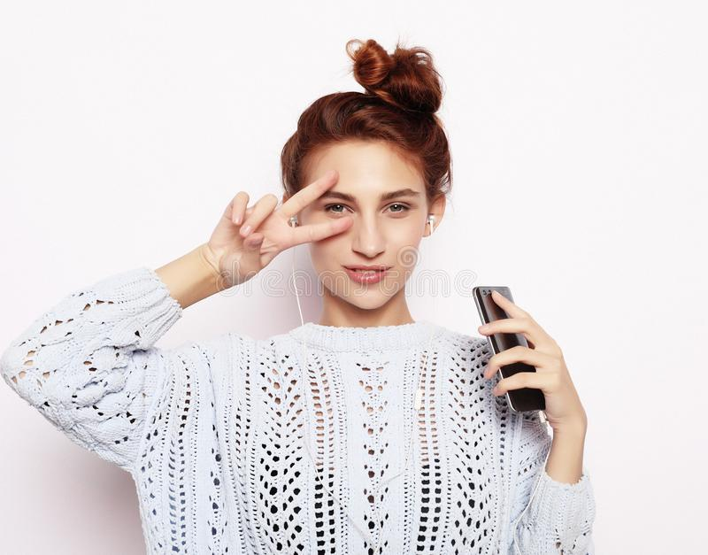 Portrait of a satisfied casual girl holding mobile phone and showing ok gesture royalty free stock image