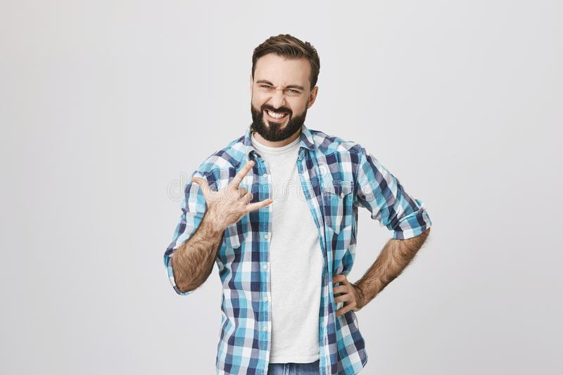 Portrait of satisfied and confident looking bearded man, holding one hand on waist and making rock gesture with another stock images