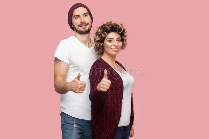 Portrait of satisfied couple of friends in casual style standing, hugging and showing thumbs up sign, looking at camera. Isolated, indoor, studio shot, pink stock photography