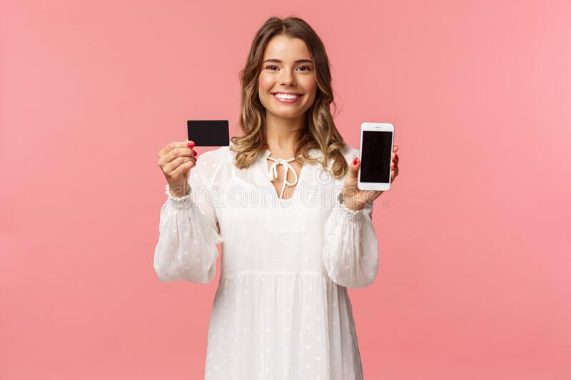 Portrait of satisfied cute blond girl in white dress, showing you her credit card and mobile phone application, online. Shopping app or bank website, smiling royalty free stock photography