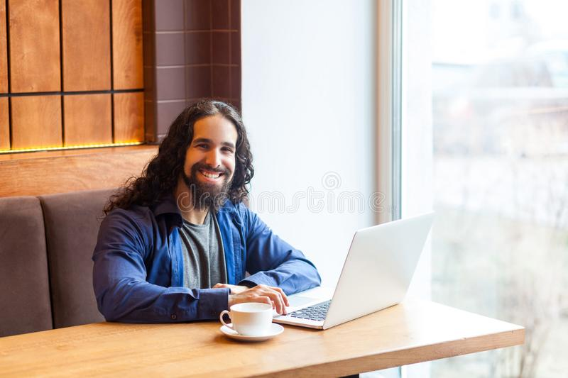 Portrait of satisfied handsome intelligence bearded young adult man freelancer in casual style sitting in cafe and working in royalty free stock photography