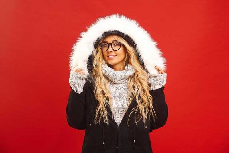 Portrait of satisfied woman, wearing a warm winter jacket with hood, has joyful expression, feels warm and comfortable royalty free stock photo