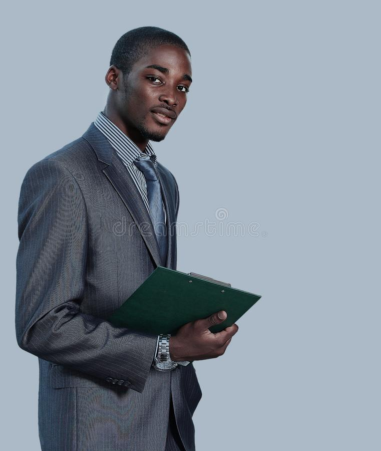 Portrait of a satisfied young African American business man with hands folded on white. royalty free stock images