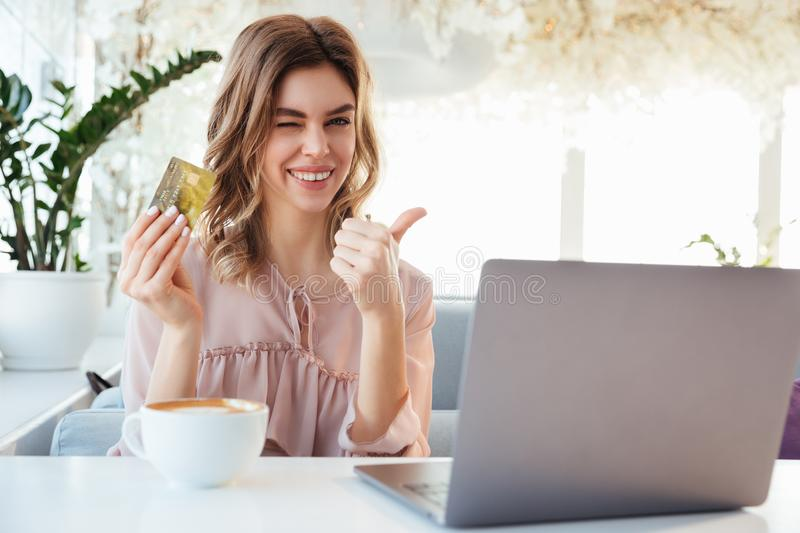 Portrait of a satisfied young woman. Holding goldern credit card and showing thumbs up while sitting with laptop computer at a cafe table indoors royalty free stock photography