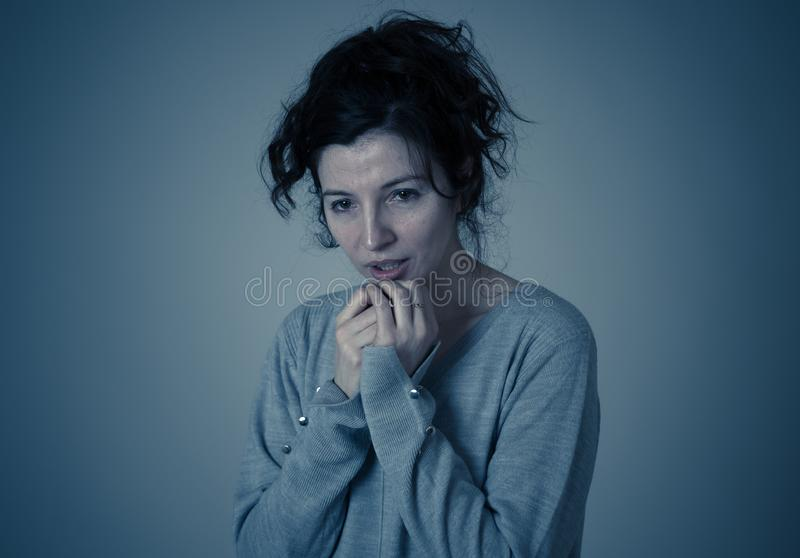 Portrait of scared and intimidated woman. Studio shot in moody light. Human expressions and emotions royalty free stock photography