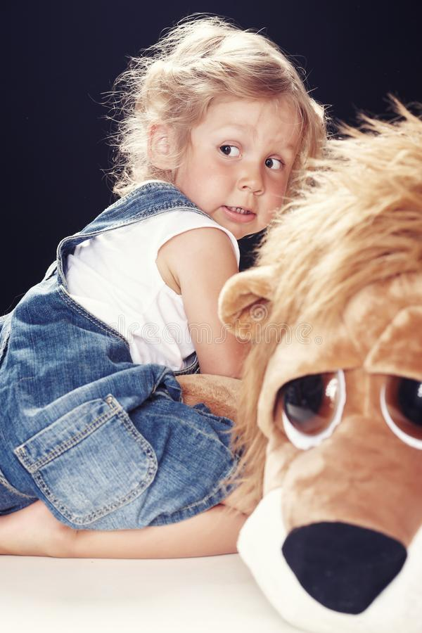 Portrait of a scared little girl in denim overalls, sitting in a studio on black background. royalty free stock photo