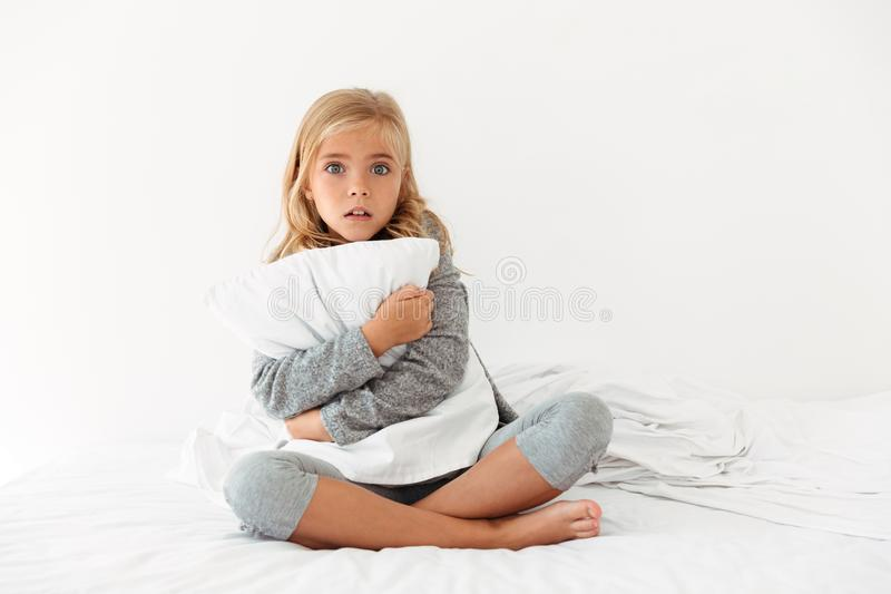 Portrait of a scared little girl hugging pillow royalty free stock images