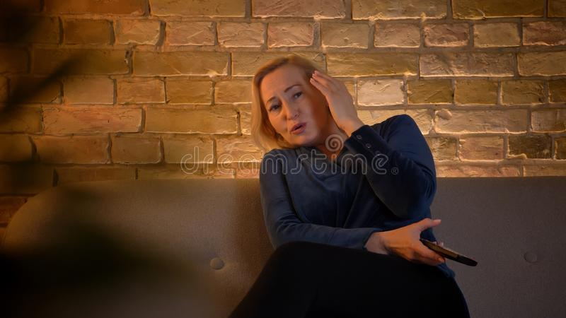 Portrait of scared senior caucasian lady watching horror movie and hiding with hand in cozy home atmosphere. Portrait of scared senior caucasian lady watching stock photos