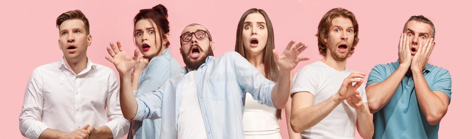 Portrait of the scared women and men on pink. I`m afraid. Fright. Portrait of the scared women and men. Business people standing isolated on trendy pink studio stock images