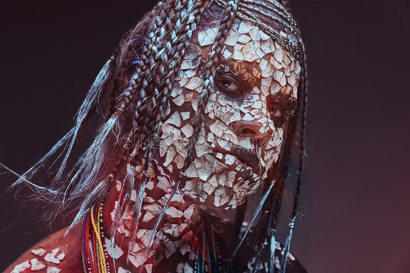 Portrait of a scary African shaman female with a petrified cracked skin and dreadlocks. Make-up concept. stock photos