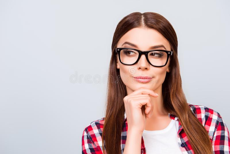 Portrait of sceptic young freelancer brown haired lady, she is i. N glasses, casual wear, on pure light background. So pensive and royalty free stock photography