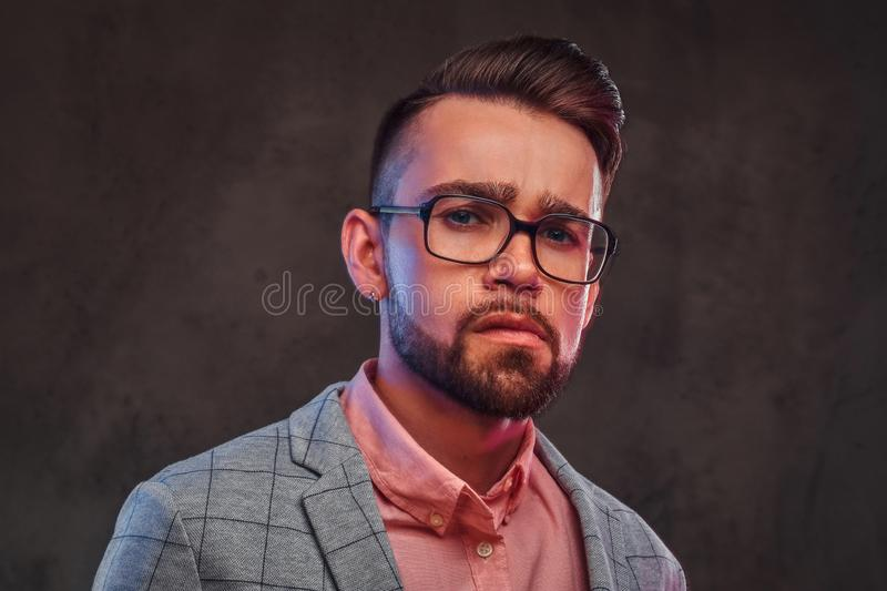 Portrait of sceptical proud man in checkered blazer, pink shirt and glasses.  royalty free stock photo