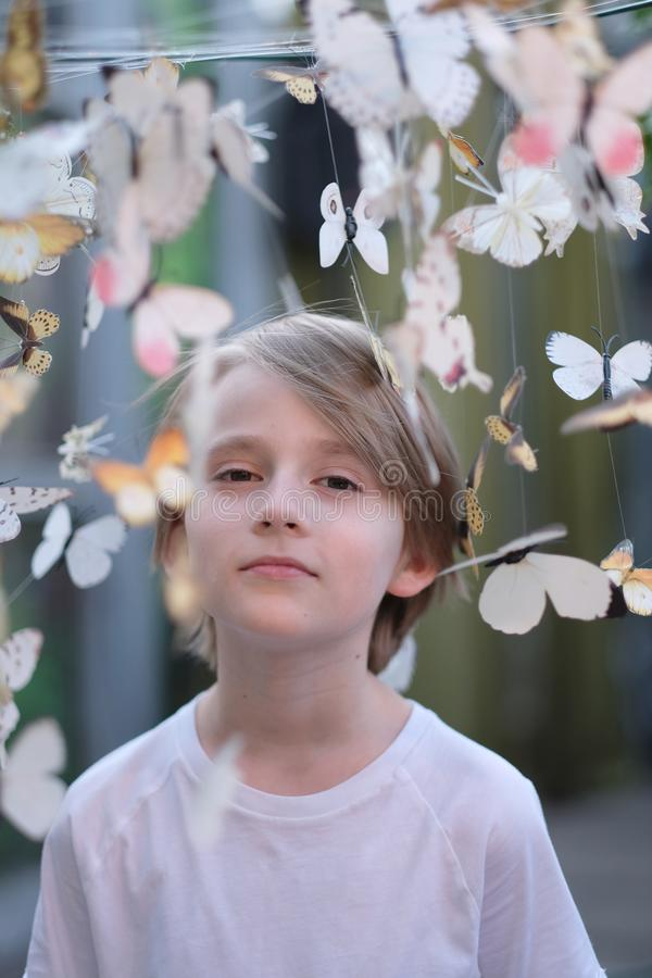 Portrait of a child among paper butterflies stock images