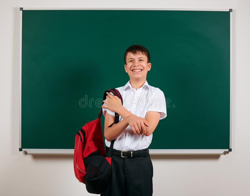 Portrait of a school boy posing with backpack on blackboard background - back to school and education concept stock photography