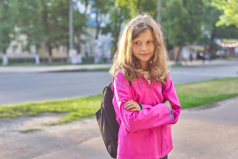 Portrait of school girl in jacket with backpack stock images