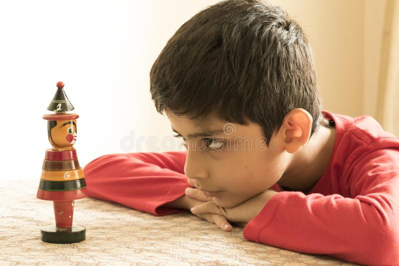 A school kid looking at a wooden toy. A portrait of a school kid staring at one of his wooden toys royalty free stock image