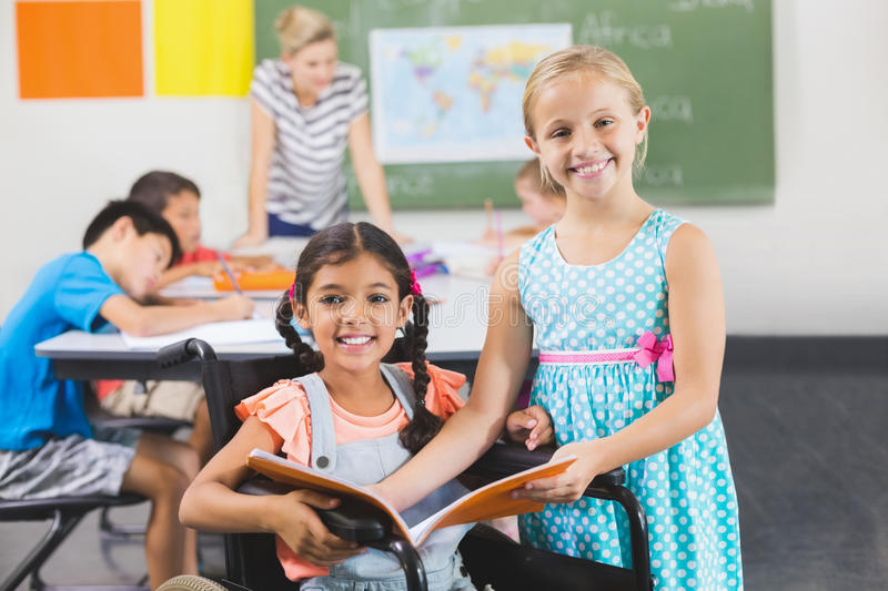 Portrait of school kids holding book in classroom royalty free stock photography