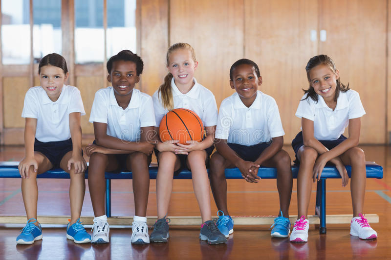 Portrait of school kids sitting in basketball court royalty free stock photography