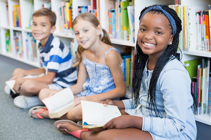 Portrait of school kids sitting on floor and reading book in library stock photography