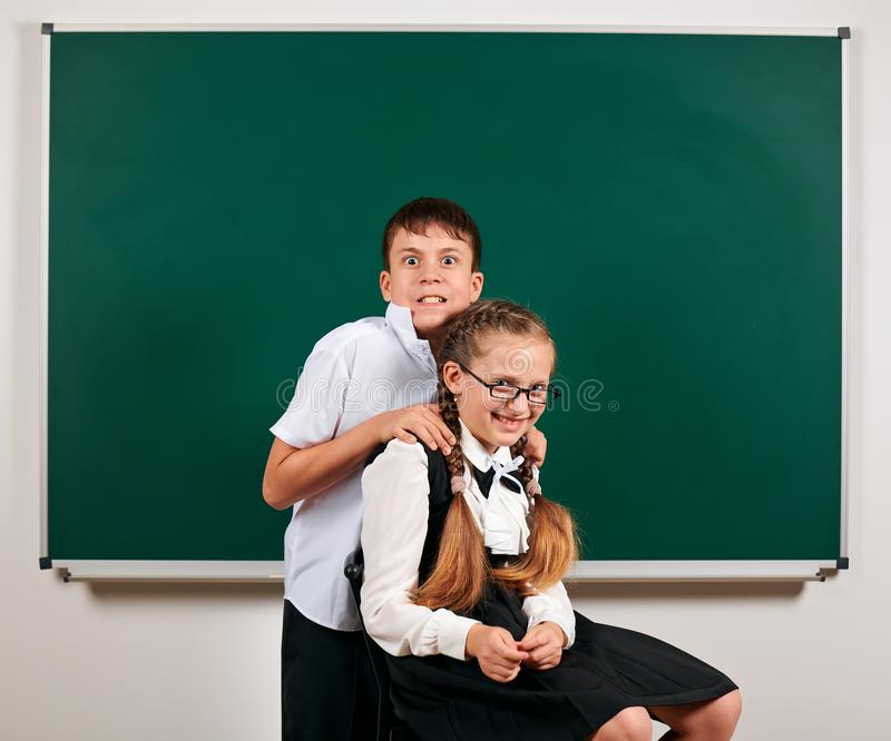 Portrait of a schoolboy and schoolgirl playing near blackboard background - back to school and education concept stock images