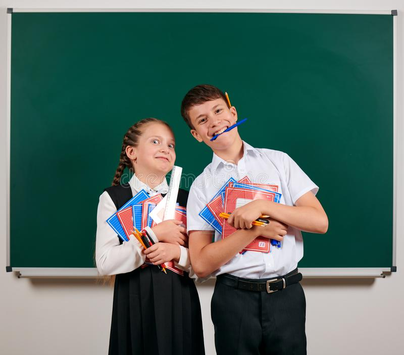 Portrait of a schoolboy and schoolgirl posing with exercise books, pens, pencils and other school supplies on blackboard stock image