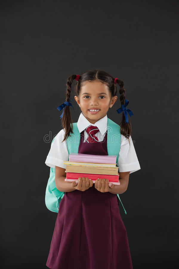 Portrait of schoolgirl in school uniform holding books against blackboard stock photos