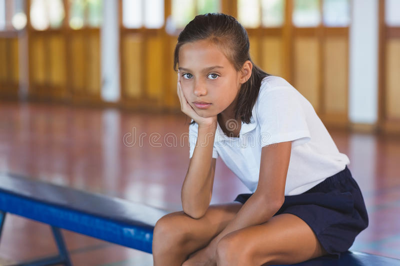 Portrait of schoolgirl sitting in basketball court royalty free stock image