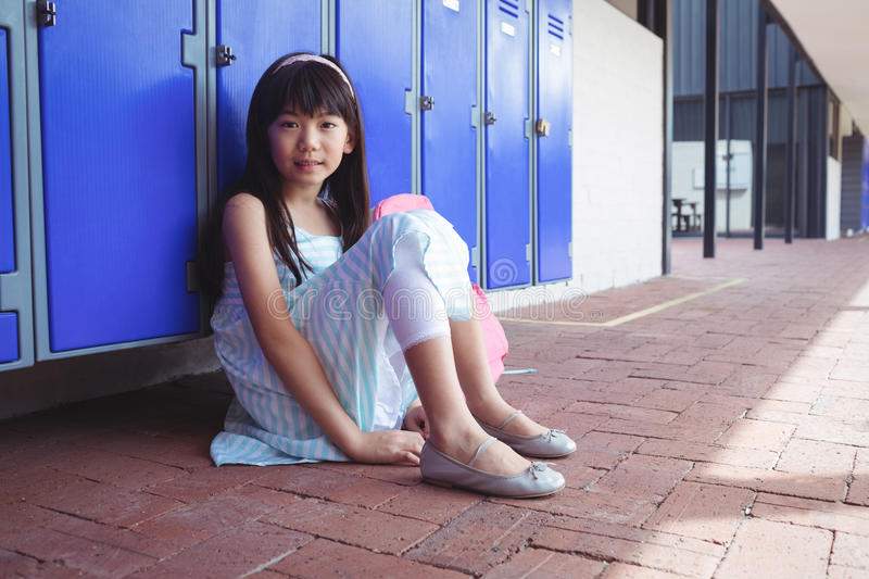 Portrait of schoolgirl sitting on pavement by lockers stock photography