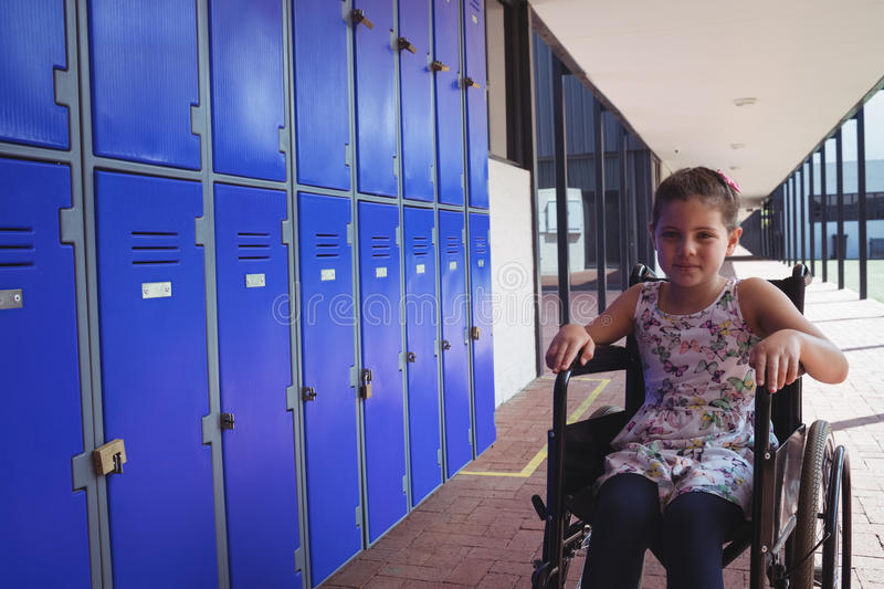 Portrait of schoolgirl sitting on wheelchair by lockers stock images