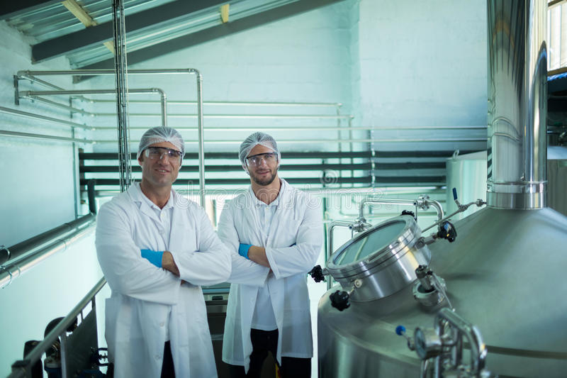 Portrait of scientists with arms crossed standing in factory royalty free stock image
