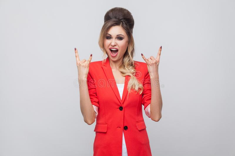 Portrait of screaming beautiful business lady with hairstyle and makeup in red fancy blazer, standing with rock sign and looking. At camera. indoor studio shot stock photography