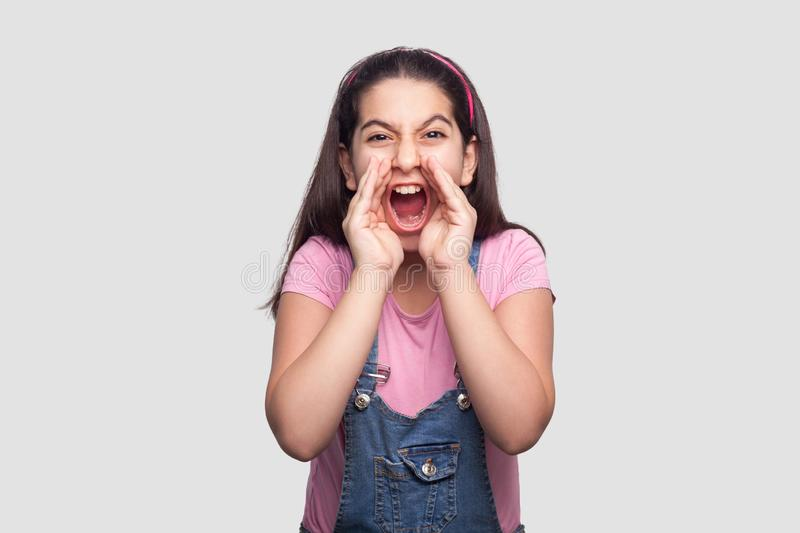 Portrait of screaming brunette young girl in casual style, pink t-shirt and blue denim overalls standing looking with hand near stock photography